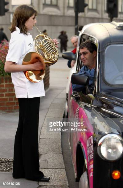 Katherine Dawkins a member of the London Philharmonic Orchestra Scholarship Scheme plays the french horn to black cab driver Stephen Clowd in central...