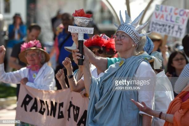 Katherine Forrest of the group Raging Grannies holds up a torch during Tech Stands Up a rally against President Donald Trump in Palo Alto California...