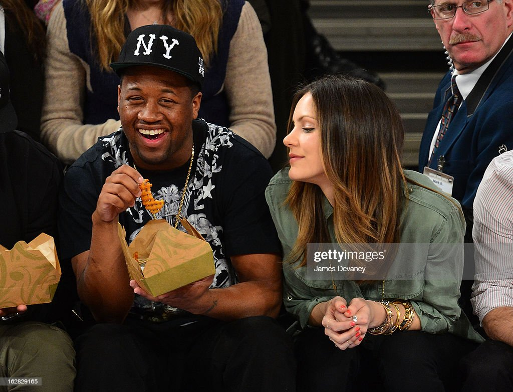 Katherine McPhee and guest (L) attend the Golden State Warriors vs New York Knicks game at Madison Square Garden on February 27, 2013 in New York City.