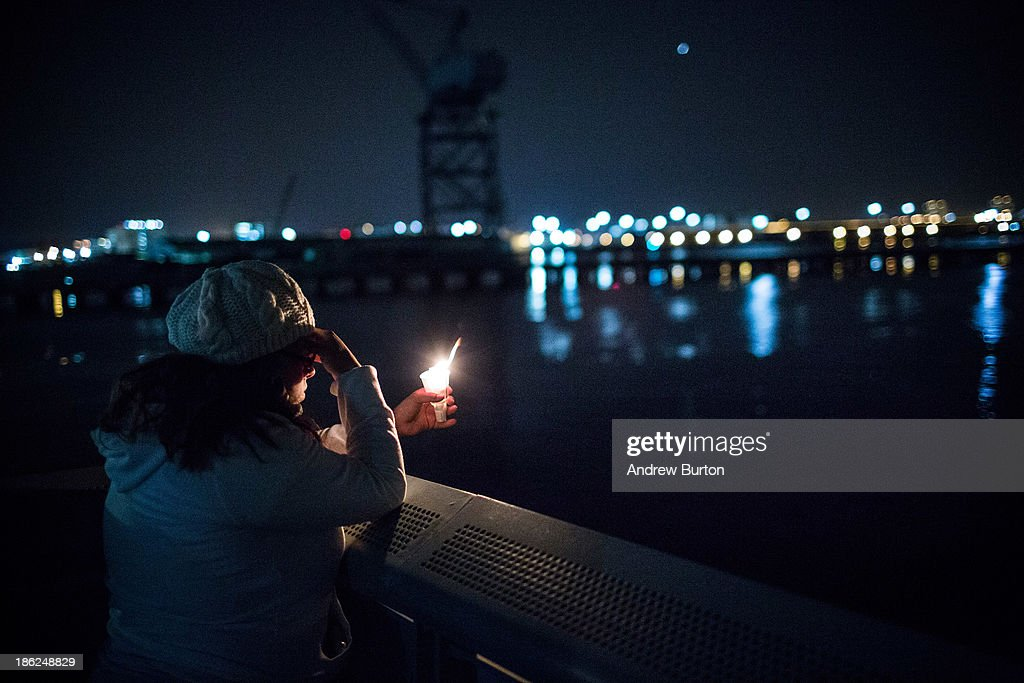 Kathleen Antonetty, a resident of the Red Hook neighborhood of Brooklyn, says a prayer while holding a candle during a vigil on the Red Hook water front to commemorate the one year anniversary of Superstorm Sandy hitting New York, on October 29, 2013 in Red Hook neighborhood of the Brooklyn borough of New York City. Vigil attendees marched through Red Hook to the water front holding candles, and were led by a marching band. Superstorm Sandy hit New York one year ago today, bringing a high tide of up to 18 feet above normal in some areas, killing hundreds and causing billions of dollars in damage. The Red Hook neighborhood of Brooklyn was hit especially hard.