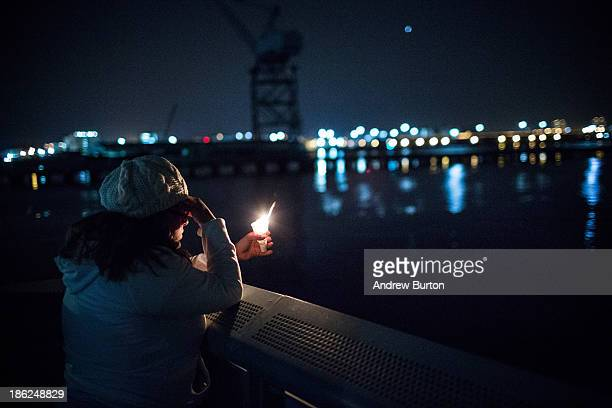 Kathleen Antonetty a resident of the Red Hook neighborhood of Brooklyn says a prayer while holding a candle during a vigil on the Red Hook water...