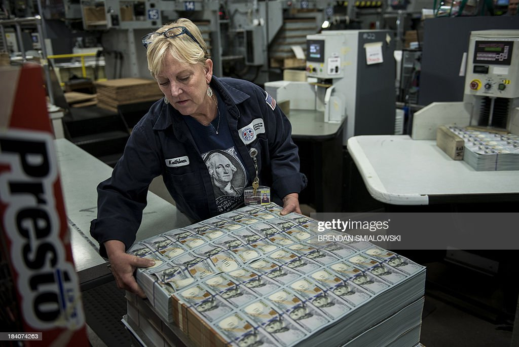 Kathleen Harmon stacks rejected sheets of the 100 USD bills before they are destroyed at the US Bureau of Engraving and Printing's Western Currency Facility on October 11, 2013 in Fort Worth, Texas. The facility is currently the sole producer of the new 100 USD bill. The bill went into circulation on October 8 and includes new security features such as a purple band with moving images, ink that changes color with the angle as well as a new more colorful design.