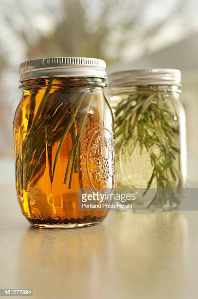 Kathleen Savoie makes up a batch of herbal vinegars at the University of Maine's Cooperative Extension in Falmouth Canning jars of herbal vinegars...