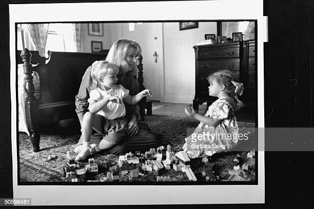 Kathleen Tobin Krueger wife of TX Sen Bob Krueger chatting w 3yrold daughter Sarah as 4yrold daughter Mariana sits on her lap while playing w Lego...