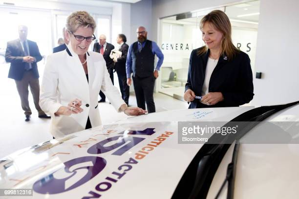 Kathleen Wynne premier of Ontario left prepares to sign the hood of a vehicle as Mary Barra chief executive officer of General Motors Corp stands...
