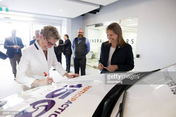Kathleen Wynne premier of Ontario left signs the hood of a vehicle as Mary Barra chief executive officer of General Motors Corp smiles after a...