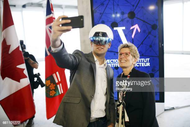 Kathleen Wynne premier of Ontario right poses for a selfie photograph with a man wearing a virtual reality helmet in the Vector Institute at the MaRS...
