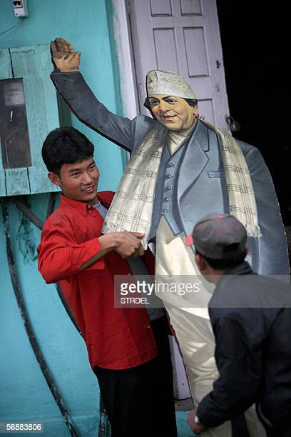 Nepali youths carry a twodimentional cutout of King Tribhuvan grandfather of Nepal's current monarch King Gyanendra to a storage room following the...