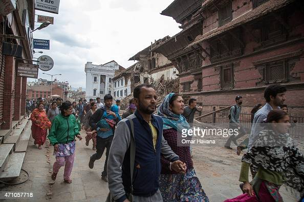 Kathmandu residents run to shelters after a replica tremor hit the city on April 25 2015 in Kathmandu Nepal More than 100 people have died as tremors...