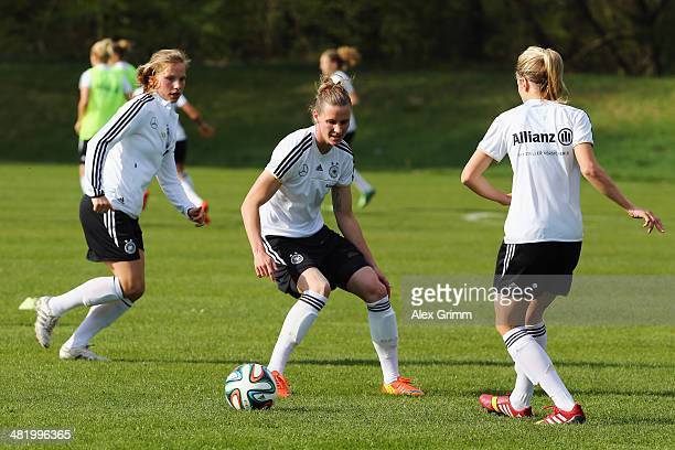 Kathrin Hendrich is challenged by Simone Laudehr and Tabea Kemme during a Germany Women's training session at the Commerzbank Arena training ground...
