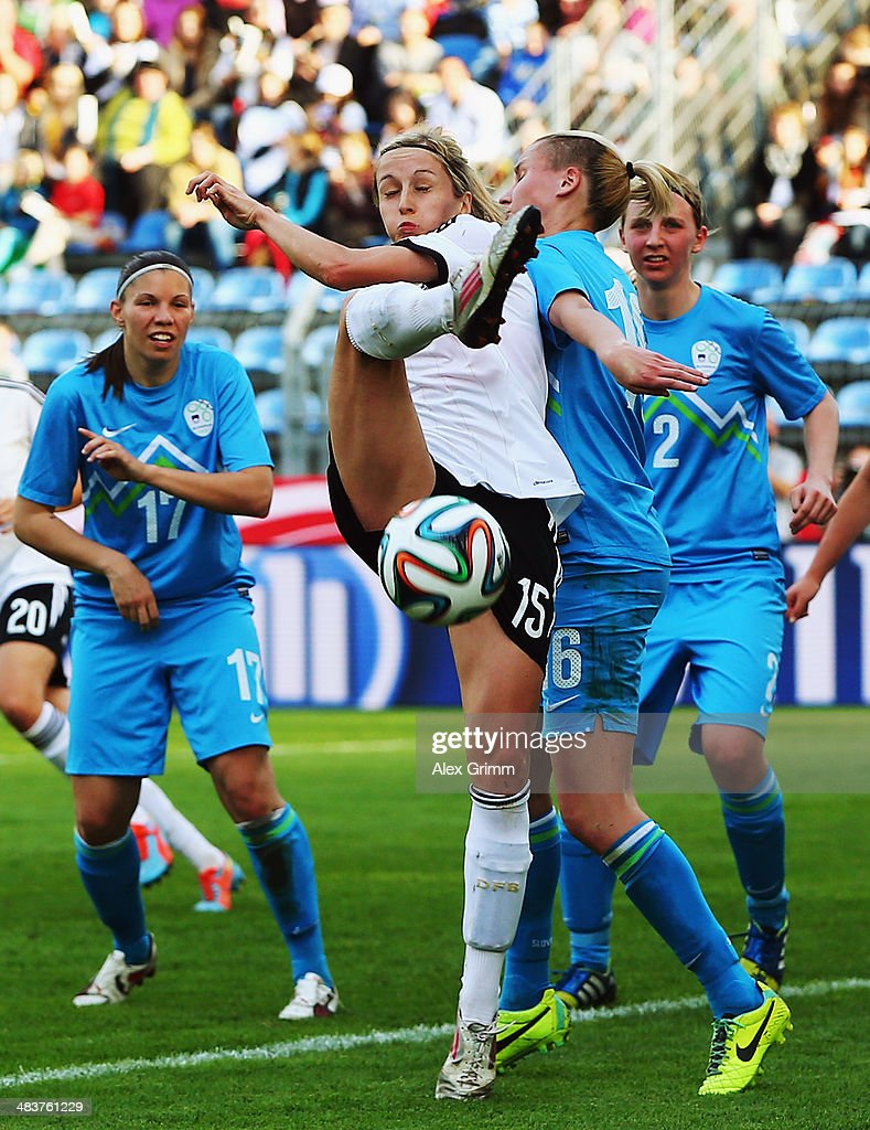 Kathrin Hendrich (C) of Germany is challenged by Urska Zganec (L) and Kaja Erzen (R) of Slovenia during the FIFA Women's World Cup 2015 qualifying match between Germany and Slovenia at Carl-Benz-Stadion on April 10, 2014 in Mannheim, Germany.