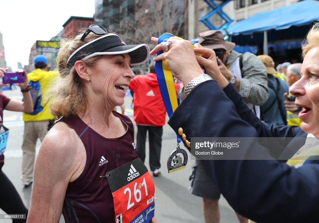 Kathrine Switzer is welcomed across the finish line by BAA President Joann Flaminio after she complete the 121st Boston Marathon on April 17, 2017.