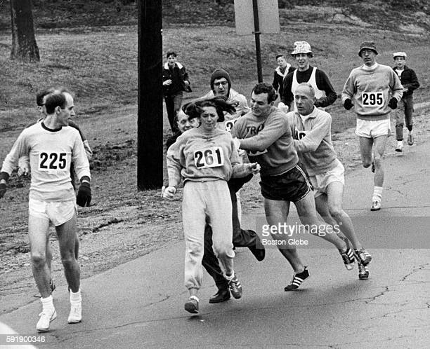 Kathrine Switzer of Syracuse NY center was spotted early in the Boston Marathon by Jock Semple center right who tried to rip the number off her shirt...