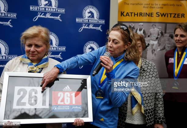 Kathrine Switzer right points to her bib number being held by BAA President Joann Flaminio as she thanks the crowd during a ceremony to have her bib...