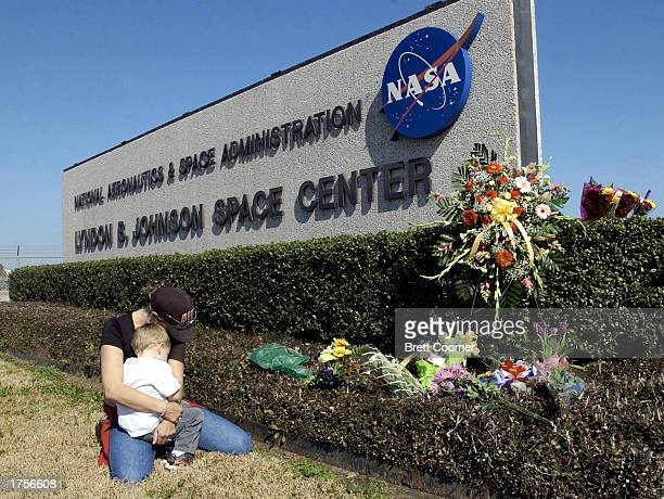 Kathryn O'Neill and her son Zachary of Laguna Hills California kneel by the entrance sign of NASA's Johnson Space Center where a makeshift memorial...