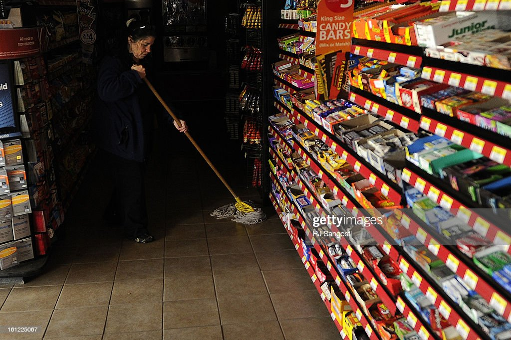 Kathy Baxter cleans the floor in the dark, Friday April, 27, 2012, as she work at the Loaf n' Jug in Lamar. Power was out in the area due to a tornado that went through town last night. The store remained open for customers who had cash. RJ Sangosti, The Denver Post