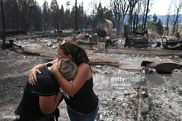 Kathy Besk cries with her daughter Shelley Besk as they stand in the burnedout ruins of their home on September 16 2014 in Weed California Fueled by...