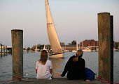 Kathy Jones left and Carla Clemens watch the racing sailboats cross the finish line from the dock at the Annapolis Yacht Club which has sponsored the...