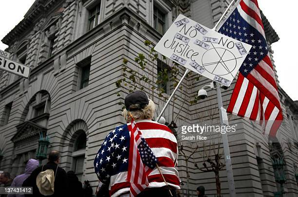 Kathy Trevino of San Francisco California holds a flags upside down in protest at the 9th Circuit Court of Appeals as part of 'Occupy Wall Street...