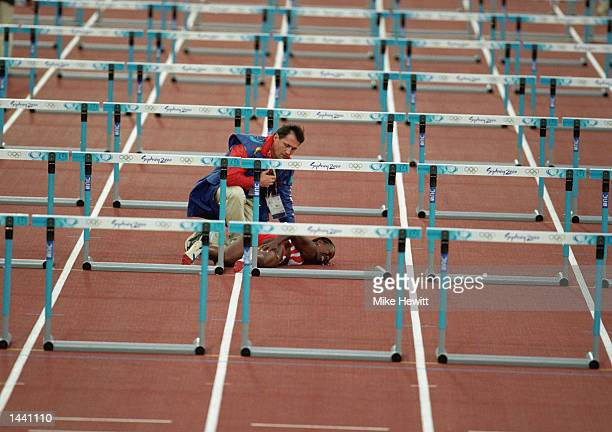 Katie Anderson of Toronto Canada grimaces in pain as a track official comes to her aid after pulling a hamstring in the second round heat of the...