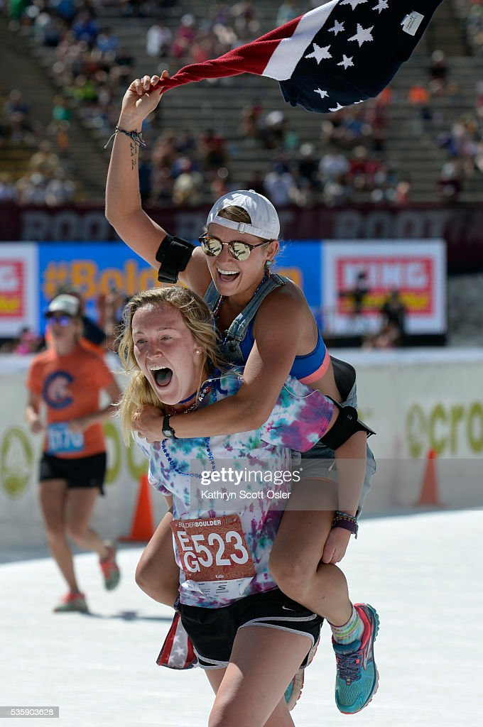 Katie Averdick, left, gives friend Morgan Judy a lift across the finish line. The two live in Estes Park. The 38th BolderBOULDER takes place along Boulder's streets with the finish line of the 10k race at Folsom Field on the University of Colorado campus on Monday, May 30, 2016.