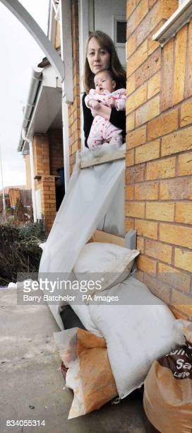 Katie Bateman with her ten week old daughter looks from her front door which is protected by sandbags on a housing estate at Longlevens near...