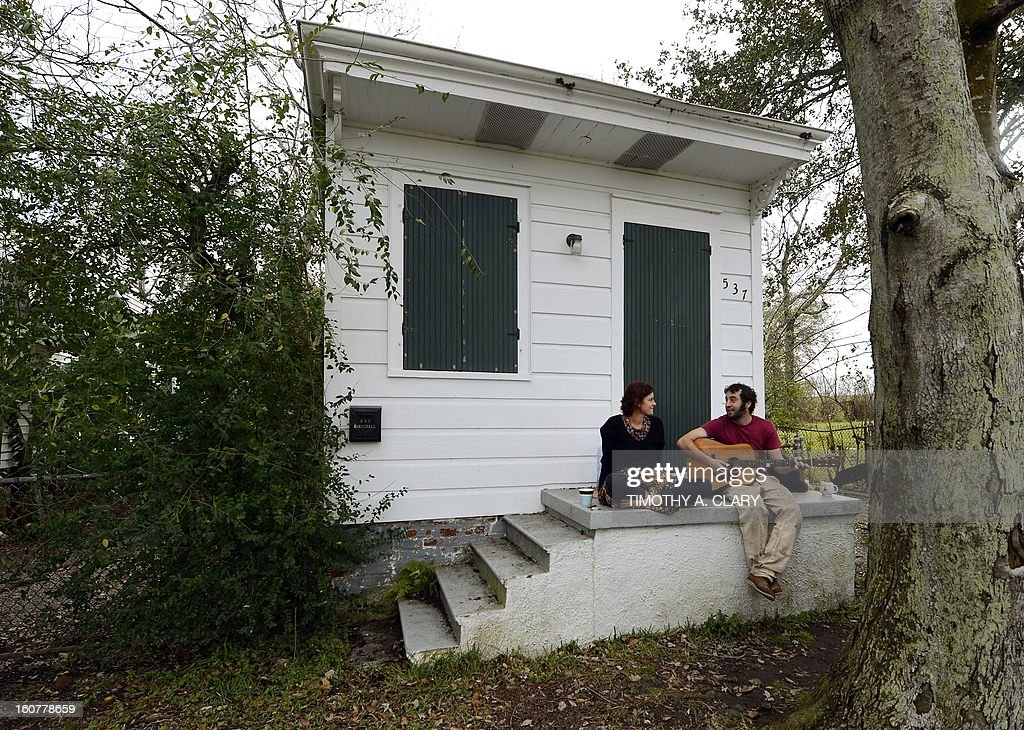 Katie Cavazos and Luke Bell sit in front of their home in the Lower Ninth Ward of New Orleans February 5, 2013. This area suffered the worst damage from Hurricane Katrina that occured in 2005 after multiple breaches in the levees of at least four canals. As of March 2009, hundreds of houses have been rebuilt, and dozens of new homes have been constructed. AFP PHOTO / TIMOTHY A. CLARY ++MORE AVAILABLE ON IMAGEFORUM++