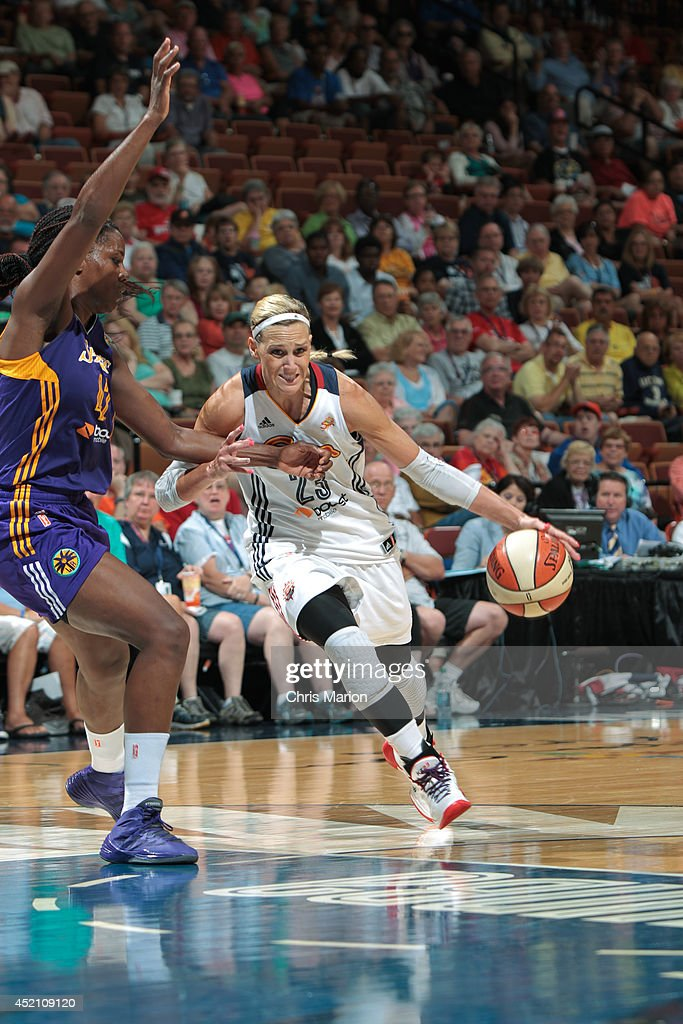 Katie Douglas of the Connecticut Sun drives the ball into the paint under pressure from Jantel Lavender of the Los Angeles Sparks during a game at...