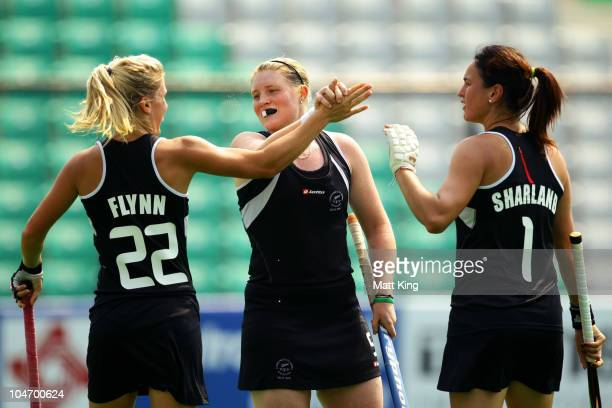 Katie Flynn of New Zealand celebrates her second goal with team mates Gemma Flynn and Kayla Sharland competes in the women's hockey match between New...