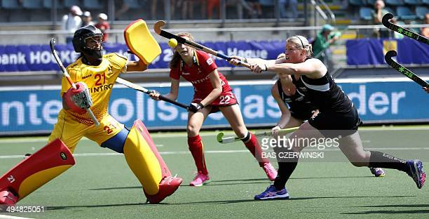 Katie Glynn of New Zealand vies with Belgium goalkeeper Aisling D'Hooghe during the Field Hockey World Cup 2014 match between New Zealand and Belgium...
