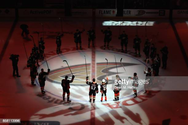 Katie Hawley a cancer patient joins Rickard Rakell and Corey Perry of the Anaheim Ducks during the opening ceremonies prior to a game against the...