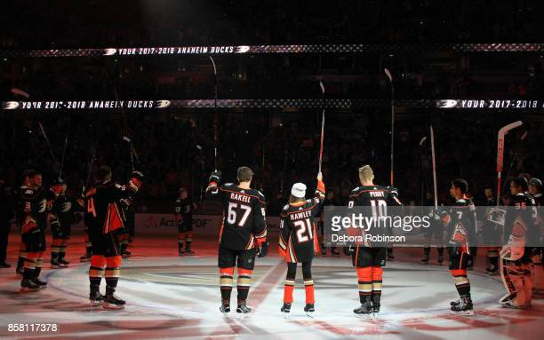 Katie Hawley this year's '21st Duck' signals to the crowd with Rickard Rakell Corey Perry and the rest of the Anaheim Ducks prior to the game against...