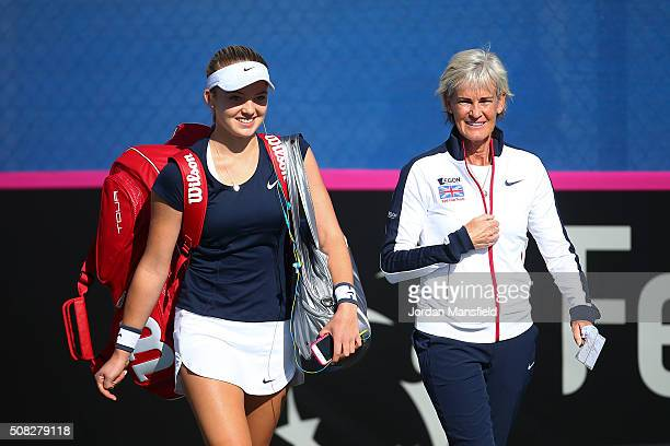 Katie Swan of Great Britain walks out with Captain Judy Murray ahead of her match against Ilze Hattingh of South Africa during the tie between South...