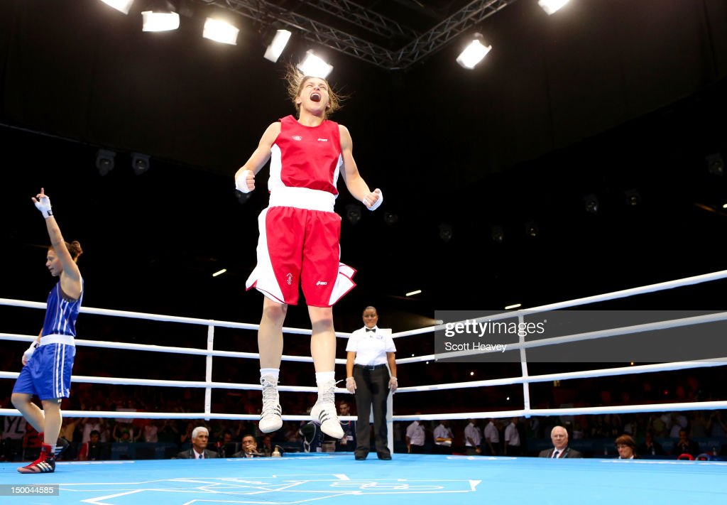 Katie Taylor (C) of Ireland celebrates winning her bout against <a gi-track='captionPersonalityLinkClicked' href=/galleries/search?phrase=Sofya+Ochigava&family=editorial&specificpeople=9327771 ng-click='$event.stopPropagation()'>Sofya Ochigava</a> (L) of Russia during the Women's Light (60kg) Boxing final bout on Day 13 of the London 2012 Olympic Games at ExCeL on August 9, 2012 in London, England.