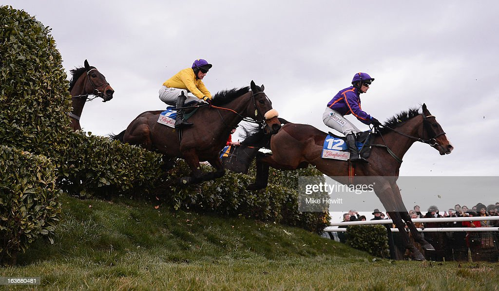 Katie Walsh on Shakervilz (R) leads <a gi-track='captionPersonalityLinkClicked' href=/galleries/search?phrase=Paul+Carberry&family=editorial&specificpeople=171766 ng-click='$event.stopPropagation()'>Paul Carberry</a> on Saddlers Storm over the Cheese Wedges fence in the Glenfarclas Handicap Chase on St Patrick's Thursday at Cheltenham Racecourse on March 14, 2013 in Cheltenham, England.