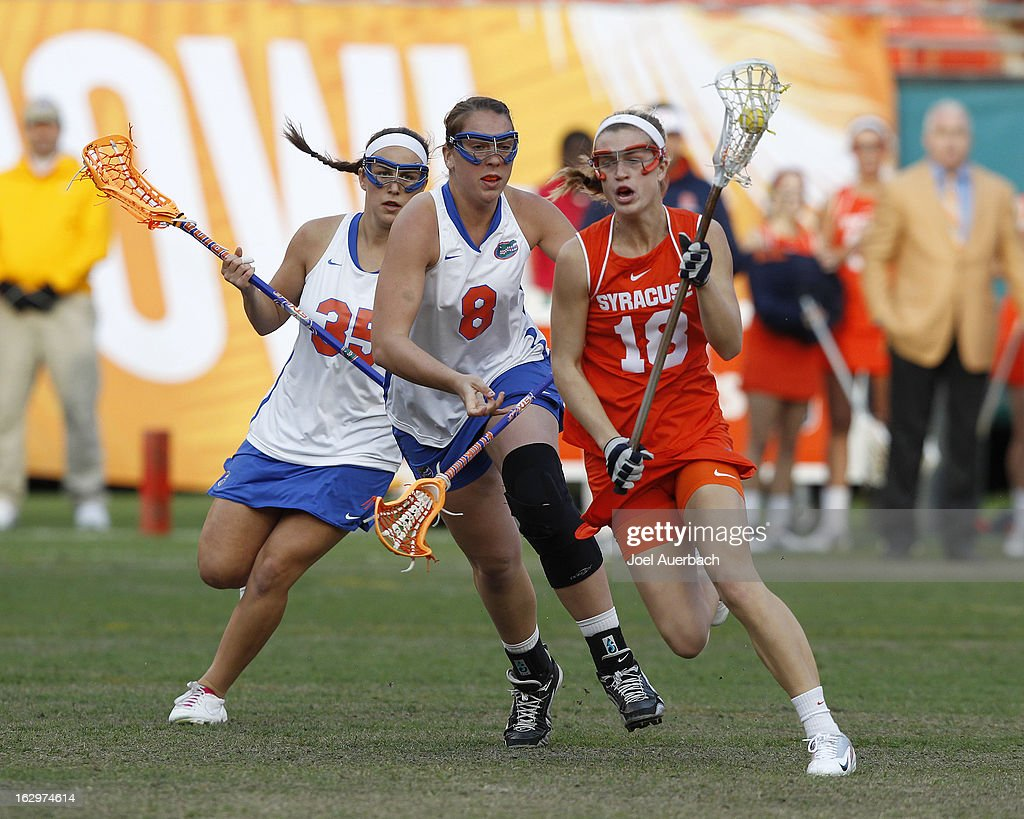 Katie Webster #18 of the Syracuse Orange brings the ball upfield while being defended by Shannon Gilroy #8 of the Florida Gators during the 2013 Orange Bowl Lacrosse Classic on March 2, 2013 at SunLife Stadium in Miami Gardens, Florida.