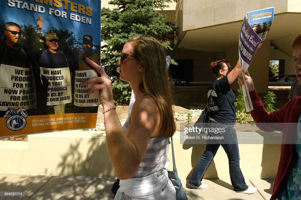 Katie Wirth, left, and her brother Joe, just to the right, Brian Heimerl, right, join others as they hold signs to protest Molson Coors' annual shareholder meeting outside at 1881 Curtis street in Denver, Colorado on May 25, 2016 in Denver, Colorado. The protestors wanted to raise concerns about the planned closure of the award-winning MillerCoors brewery in Eden, N.C. The closure will impact 450 Teamster families in that state. The decision to close Eden was announced on September 14, just two days before the merger talks between SABMiller (LON: SAB) and AB/Inbev (NYSE: BUD) were formally disclosed to the public. Teamsters will warn shareholders of the likely anticompetitive effects of that decision and how it may be viewed by regulators.