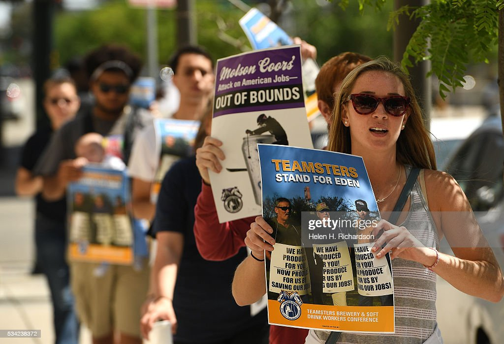 Katie Wirth, right, joins others as they hold signs to protest Molson Coors' annual shareholder meeting outside at 1881 Curtis street in Denver, Colorado on May 25, 2016 in Denver, Colorado. The protestors wanted to raise concerns about the planned closure of the award-winning MillerCoors brewery in Eden, N.C. The closure will impact 450 Teamster families in that state. The decision to close Eden was announced on September 14, just two days before the merger talks between SABMiller (LON: SAB) and AB/Inbev (NYSE: BUD) were formally disclosed to the public. Teamsters will warn shareholders of the likely anticompetitive effects of that decision and how it may be viewed by regulators.
