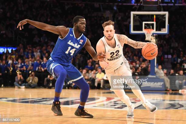 Katin Reinhardt of the Marquette Golden Eagles dribbles the ball around Ismael Sanogo of the Seton Hall Pirates during the Big East Basketball...