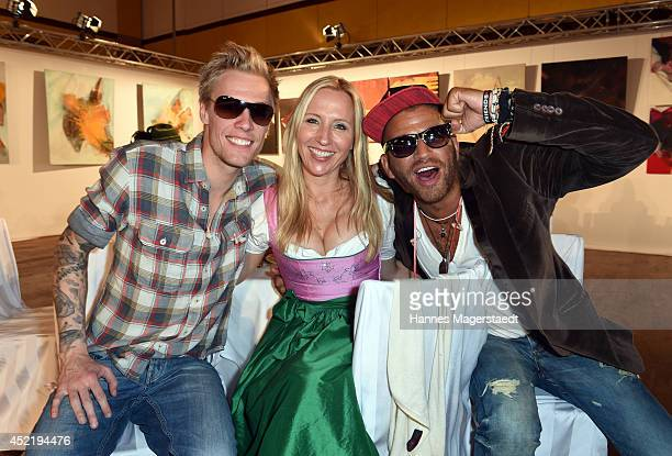 Katja Wunderlich and Rufus and P attend the Sixt ladies dirndl dinner on July 15 2014 in Munich Germany