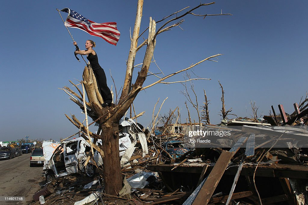 Katlyn Wilkins (in tree) and Andrea Wilkins Morelli work on securing an American flag in a tree as they deal with the destruction caused by a massive tornado that passed through the town killing at least 139 people on May 29, 2011 in Joplin, Missouri. President Barack Obama is scheduled to visit the town as it continues the process of recovering from the storm.