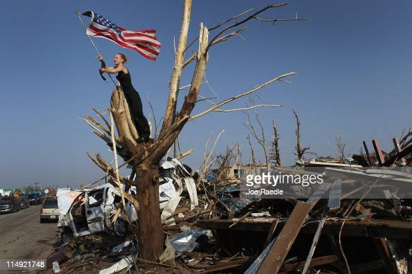 Katlyn Wilkins and Andrea Wilkins Morelli work on securing an American flag in a tree as they deal with the destruction caused by a massive tornado...