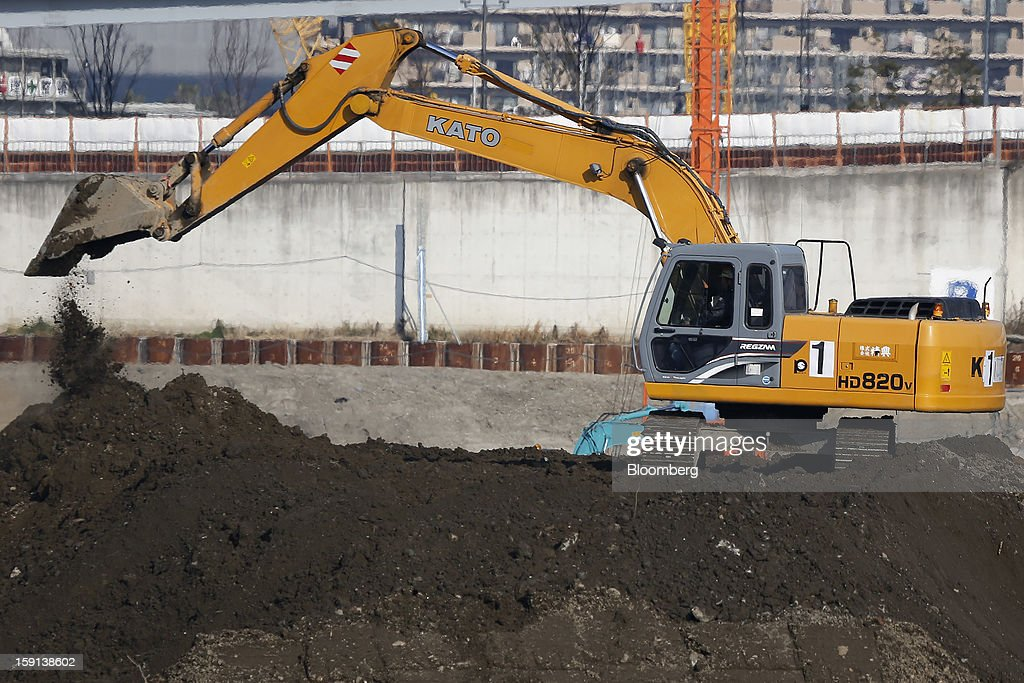 A Kato Works Co. excavator operates on a construction site in Tokyo, Japan, on Tuesday, Jan. 8, 2013. Prime Minister Shinzo Abe aims to compile Japan's economic stimulus package on Jan. 11, and seeks to have new economic growth strategy by mid-year. Photographer: Kiyoshi Ota/Bloomberg via Getty Images