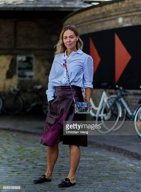 Katrin Soderlind wearing a bordeaux leather skirt a blue button shirt blouse Gucci slippers and a multi color bag outside Revolver Fair during the...