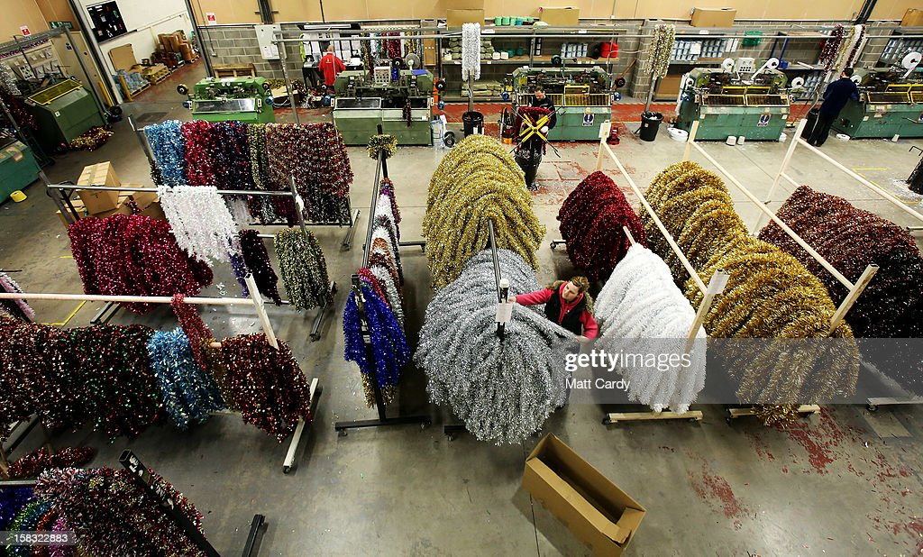 Katrina Roach sorts through recently manufactured tinsel at the Festive Productions Ltd factory, showroom, shop and warehouse on December 13, 2012 in Cwmbran, Wales. Although Christmas is less than two weeks away the staff at Festive are already planning and gearing up for Christmas 2013. The 14 acre fully integrated showroom, factory and warehouse measuring 250000 sq ft in size holds Festive Productions who are now the last manufacturer of tinsel in UK with the majority of tinsel sold in the UK also made at their factory in Wales. As well as tinsel, Festive, which is one of Europe's largest suppliers and manufacturer of Christmas and seasonal decorations, has increased its product portfolio, to include nearly every conceivable Christmas decoration category including baubles, tinsel garlands, wreaths, lights, fibre optic trees and artificial trees.