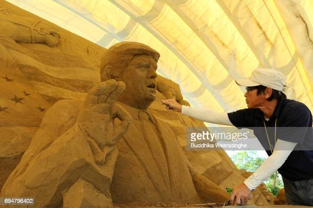 Katsuhiko Chaen a sand sculptor and executive director of the Sand Museum works on a sculpture of US President Donald Trump during the 10th Annual...