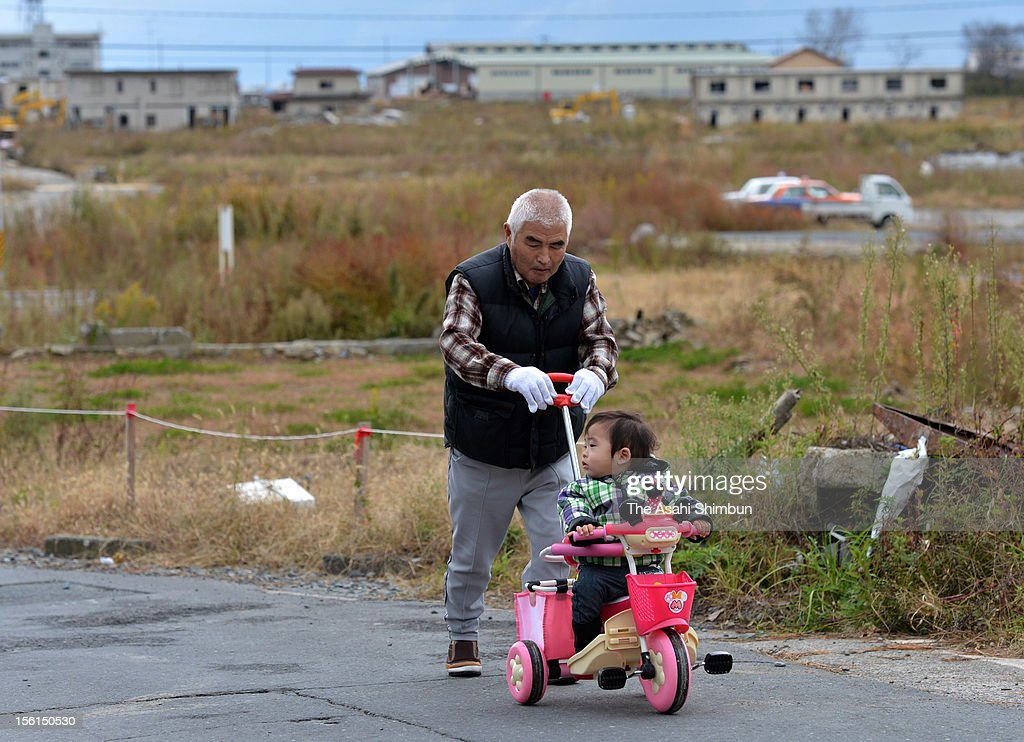 Katsuhiko Saito(75), who lost his daughter and three grandchildren by the tsunami, takes a walk with his relative's child on November 11, 2012 in Kamaishi, Iwate, Japan. Japan marks 20 months anniversary of the Great East Japan earthquake and following tsunami, occurred on March 11, 2011.