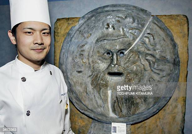 Katsunori Hirota a patissier of Shinagawa Prince Hotel stands beside his work of 'Bocca della Verit' or the Mouth of Truth made of sugar candy during...