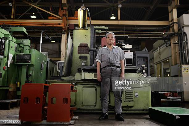 Katumi Takata chairman of Osaka Machine Tool Co poses for a photograph with his oldest piece of equipment a 'Spiramatic Jigmil' made in Michigan more...