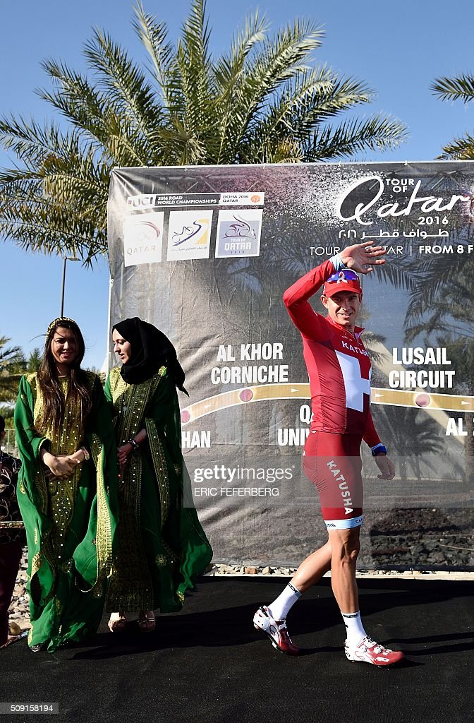 Katusha team leader Norvegian Alexander Kristoff raise his arm on the podium after he won the second stage of the 2016 Tour of Qatar cycling race, starting and finishing at the Qatar University on February 9, 2016. / AFP / Eric FEFERBERG